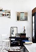 Weiss lackierter Holzstuhl und schwarzes Regal in Vintage Wohnraum