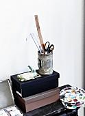 Zeichenutensilien in Dose auf Papierschachtel und Malerpaletten auf Ablage