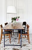 Rustikaler Tisch und Holzstühle im 60er Jahre Stil, darüber zeitgenössische Pendelleuchte mit weißem Schirm, im Esszimmer mit Holzdielenboden im Used Style