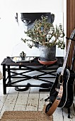 Guitar on guitar stand and house plan on dark bamboo bench