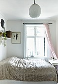 Double bed with shiny bedspread in front of window in white bedroom