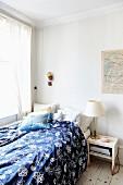 Bett mit blau-weiss gemusterter Bettwäsche, in schlichter Zimmerecke