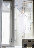 Old radio on windowsill in front of white blouse hung on open window casement