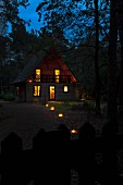 Romantic twilight atmosphere with illuminated wooden house in woodland clearing and lanterns on floor along garden path