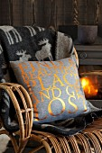 Kissen mit goldenen Buchstaben auf grauem Bezug und Plaid mit Rentier-Motiv auf Rattansessel vor Kaminfeuer