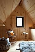 Holzverkleideter Rückzugsort unter Satteldach, Rattanstuhl mit Kissen und gemütlicher Sitzpouf auf Holzboden mit Schaffell