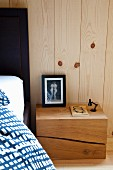 Bedside table made from solid wooden block against board wall