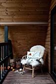 Gemütlicher Rattanstuhl mit hellem Schaffell auf Balkon, seitlich auf Holzboden Windlichter und Laternen