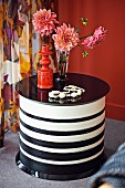 Vase of dahlias and brick-red ceramic vase on round, black and white striped coffee table in front of floral curtain