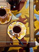 Espresso cups and saucers with floral patterns on glass table