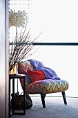 Red cushion on easy chair with zig-zag cover next to vase of twigs on side table and designer lamp