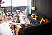 Cushions and rugs contrasting with black sofa combination and wall; view of balcony through open folding sliding glass doors