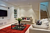 Pale sofas and red rug in front of minimalist wall with fitted cupboards and appliances in living room lit by spotlights