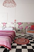 Bedroom with round rug on chequered floor, double bed with white wooden headboard and striped blanket and floral wallpaper dado