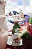 Cake stand made from stacked cups and plates with small teapot on top