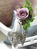 Small arrangement with dusky pink rose and grey love-heart pendants on backrest of white chair