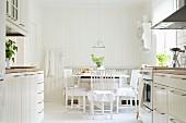 Blick von der zweizeiligen, skandinavischen Einbauküche auf Essplatz im weissen Shabby Stil