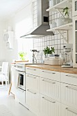 Scandinavian kitchen counter below bracket shelves and extractor hood