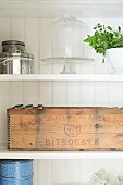 Vintage wooden crate stencilled in Swedish, tins and cake stand with glass cover on shelves