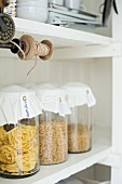Pasta in storage jars with decorated lids and vintage thread reel on white kitchen shelves