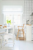 Dining area with ruched seat cushions, and high chair below window in white, Scandinavian kitchen