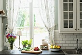 Vegetables on chopping board and vase of flowers on kitchen worksurface in front of window with gathered curtains