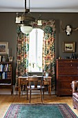 Rustic study with antique desk in front of window with pelmet and floor-length curtains