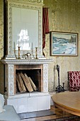 White-tiled, open fireplace with candlesticks on mantelpiece in traditional living room