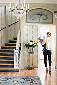 Foyer with white and blue wallpaper, curved staircase, bouquet and woman carrying baby