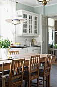 Wooden chairs around dining table in country-house kitchen with white cupboards