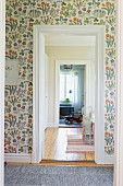Floral wallpaper on wall of foyer with open doorway and view of toy car in room beyond