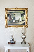 Flask and beakers on tray next to vintage oil lamp on white console table below gilt-framed picture on wall