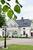 View past traditional street lamp in garden to elegant, white house with conservatory extension