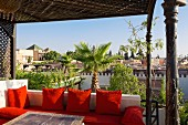 Red cushions on the roof terrace of the Riad Dar Doukkala Hotel in Marrakesh, Morocco invite you to linger