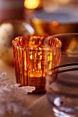 Orange tealight holder on Christmas table (close-up)