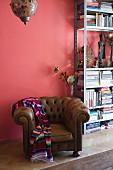 Eklektisches Flair mit traditionellem Ledersessel und Folkloreplaid vor Metall-Bücherregal an rosafarbener Wand