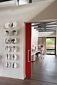 Wall plates with anatomical motifs next to open doorway with red sliding door and view into home office