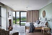 Modern bedroom with double bed opposite fireplace with firewood store; open, sliding terrace doors in background
