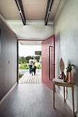 Minimalistischer Eingangsbereich, seitlich Wandtisch, im Hintergrund rot lackierte, offene Haustür und Frau mit Hund