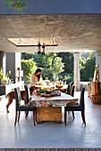 Überdachte Terrasse mit Esstisch und Stühlen, im Hintergrund Frau mit Hund