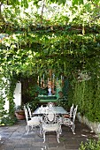Ornate, white metal chairs around table on terrace and candle chandelier hanging from pergola