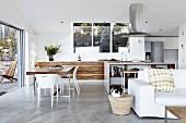 Designerküche mit Essplatz in offenem Wohnraum, im Vordergrund weiße Couch