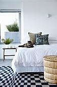 Katze auf Bett mit weisser Bettwäsche, davor schwarz-weiss karierter Teppich im Schlafzimmer