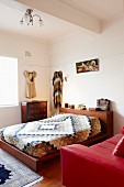 Red leather couch and patchwork bedspread on double bed in retro bedroom