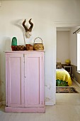 Various containers on top of pink-painted wooden cupboard below hunting trophy on wall next to open bedroom door