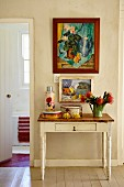 Vintage containers and vase of proteas on rustic console table below framed pictures in foyer