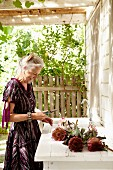 Woman with proteas on terrace with sink adjoining house