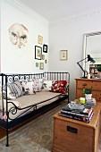 Holztruhe gegenüber schwarzem Vintage Metallbett im Wohnzimmer