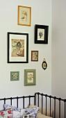 Schwarzes Metallbett an Wand und gerahmte Bilder