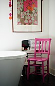 Pink-painted wooden chair next to partially visible modern bathtub and framed floral picture on wall